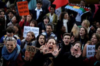 People shout slogans during a march organized by the Fridays for Future international movement of school students outside of the COP25 climate talks congress in Madrid, Spain