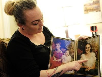 Amber Sawyer holds two framed photos with herself when she was 8, left, her sister Angela, 4, center and her oldest sister Donna, 21