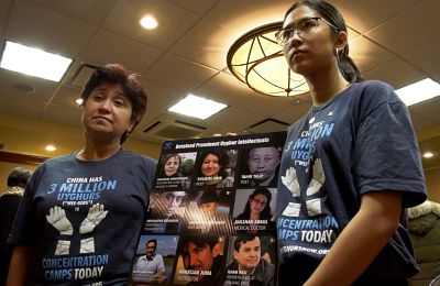 Fourteen-year-old Mehliya Cetinkaya (right) stand with her mother holding a poster with a photo of a family member forced into a detention centre in Xinjiang