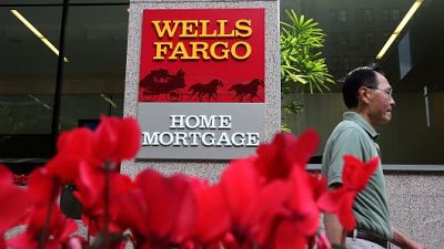 A pedestrian walks by a Wells Fargo home mortgage office in San Francisco.