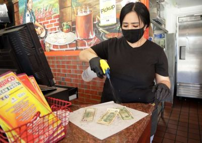 Maricela Moreno, manager at El Tarasco in Marina del Rey, disinfects cash at the restaurant