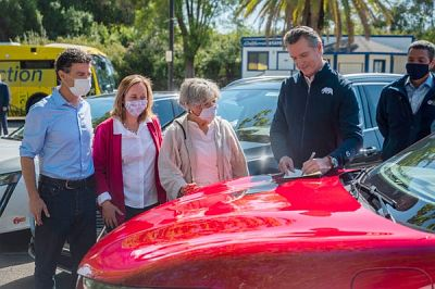 California Gov. Gavin Newsom signed an executive order banning the sale of gas-powered cars by 2035, on the hood of a Ford Mustang Mach-E