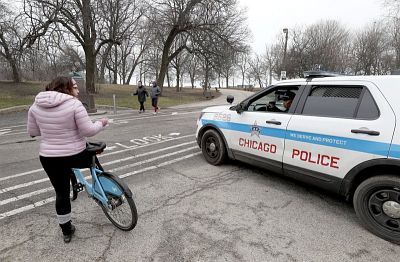 Chicago police officer notifies a cyclist that the trails in Promontory Park, along Lake Michigan, are closed in an effort to limit the spread of COVID-19 infections